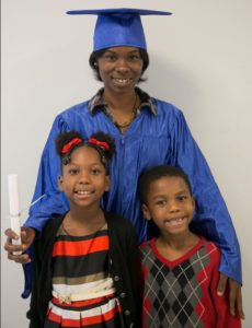 Literacy Action graduate Shanaya poses with her children in her graduation robe